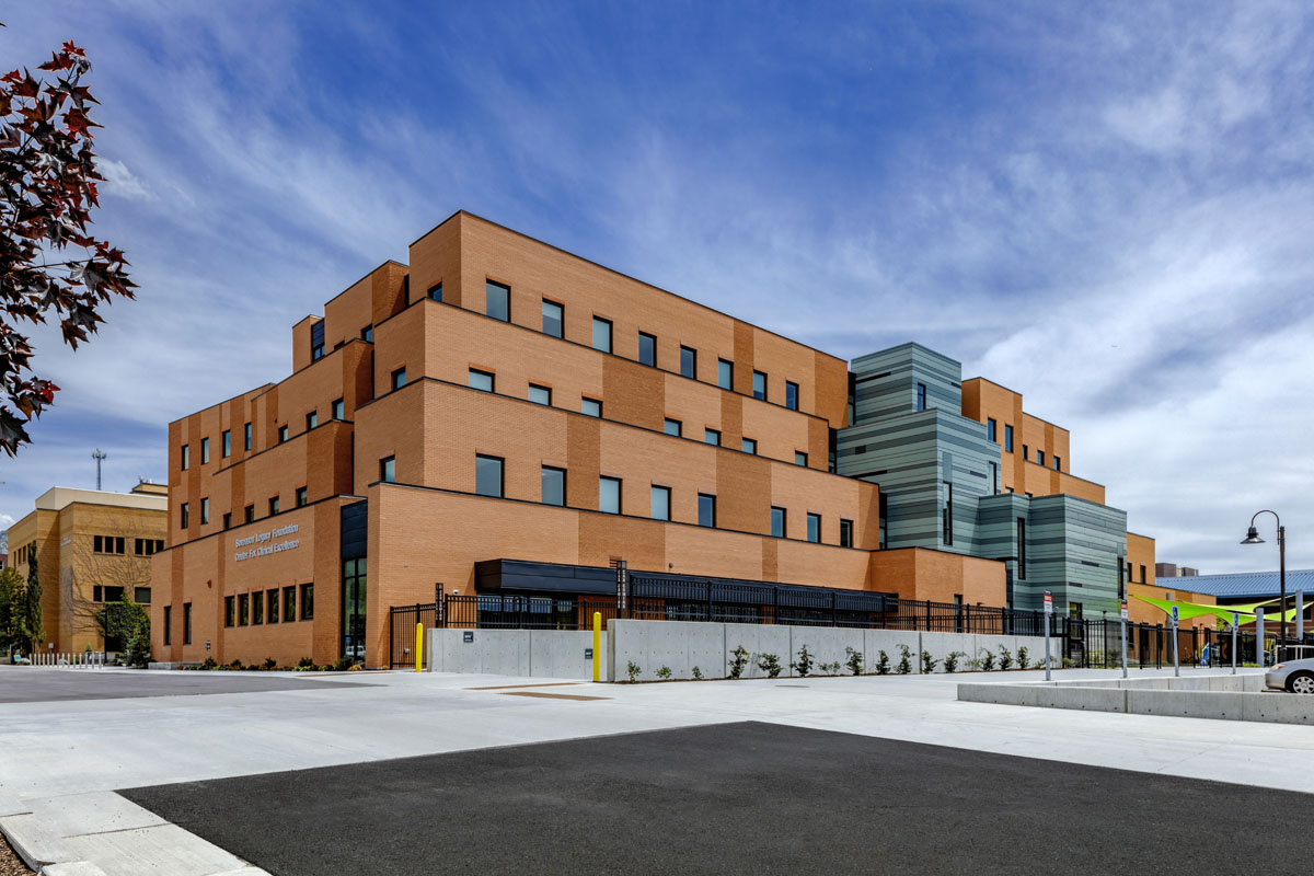 A stepped red brick healthcare design building with a cloudy blue sky above.