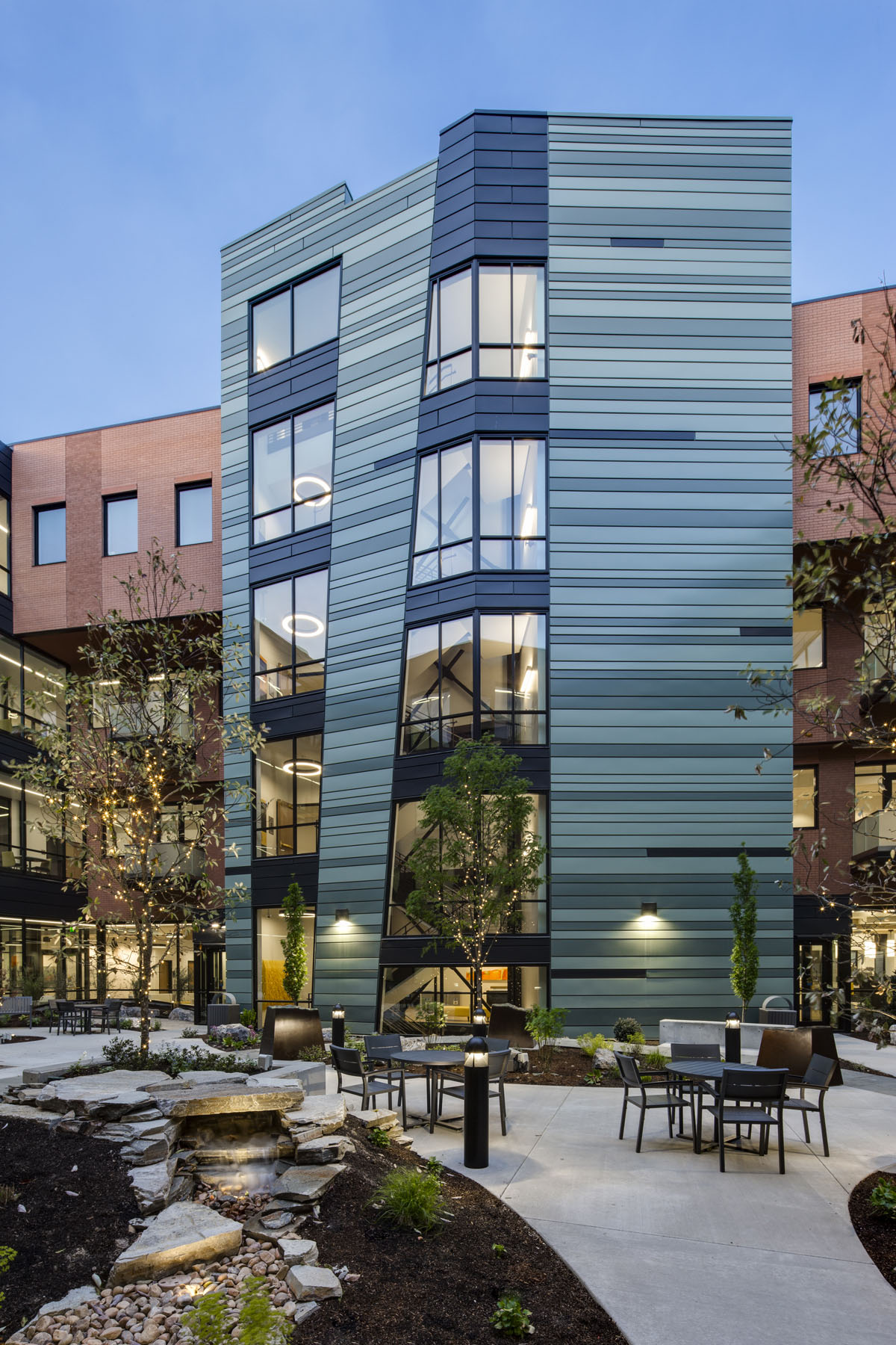 The striped exterior of the staircase stands out in the courtyard against the red brick and glass bridges as part of the healthcare design.