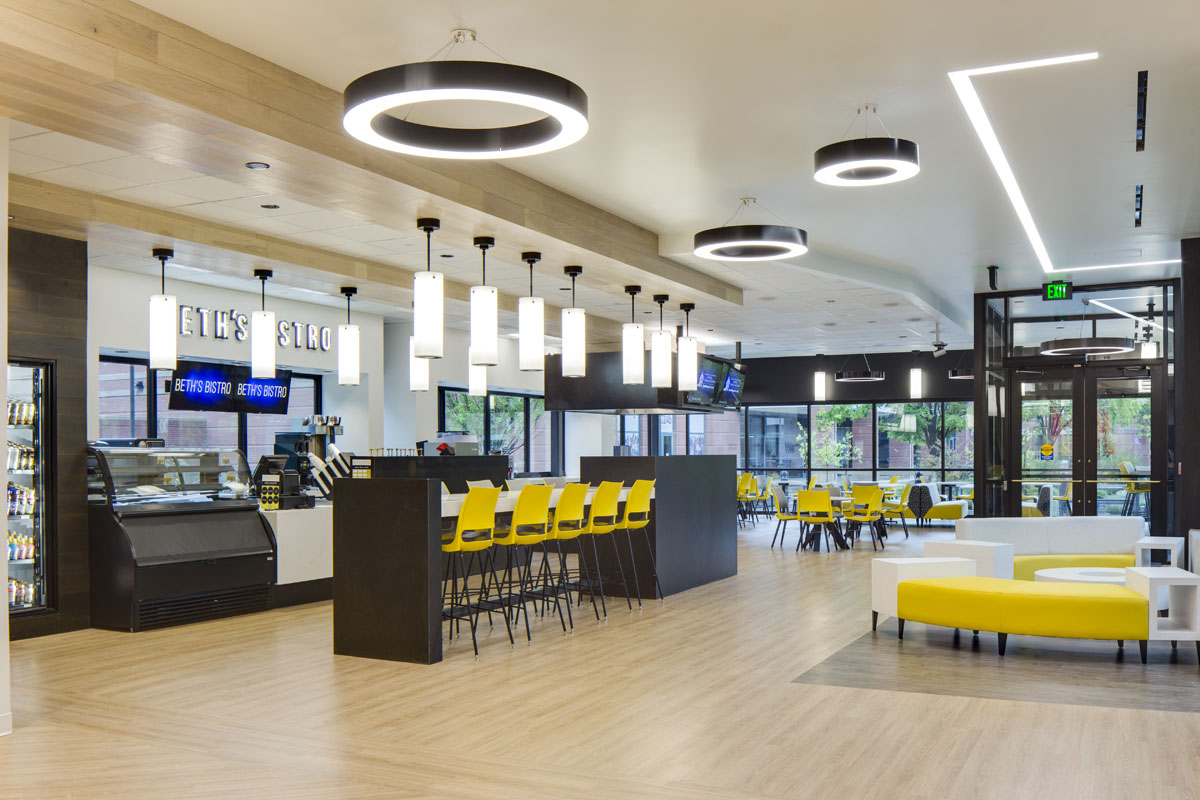 The cafe with yellow and gray seating as part of the healthcare design.