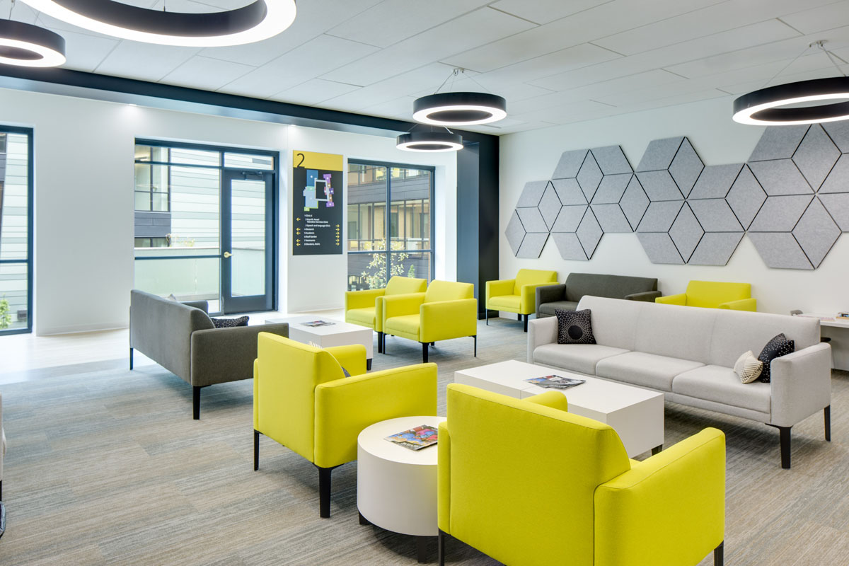 A lobby waiting area with yellow chairs and gray sofas for one of the clinics as part of the healthcare design.