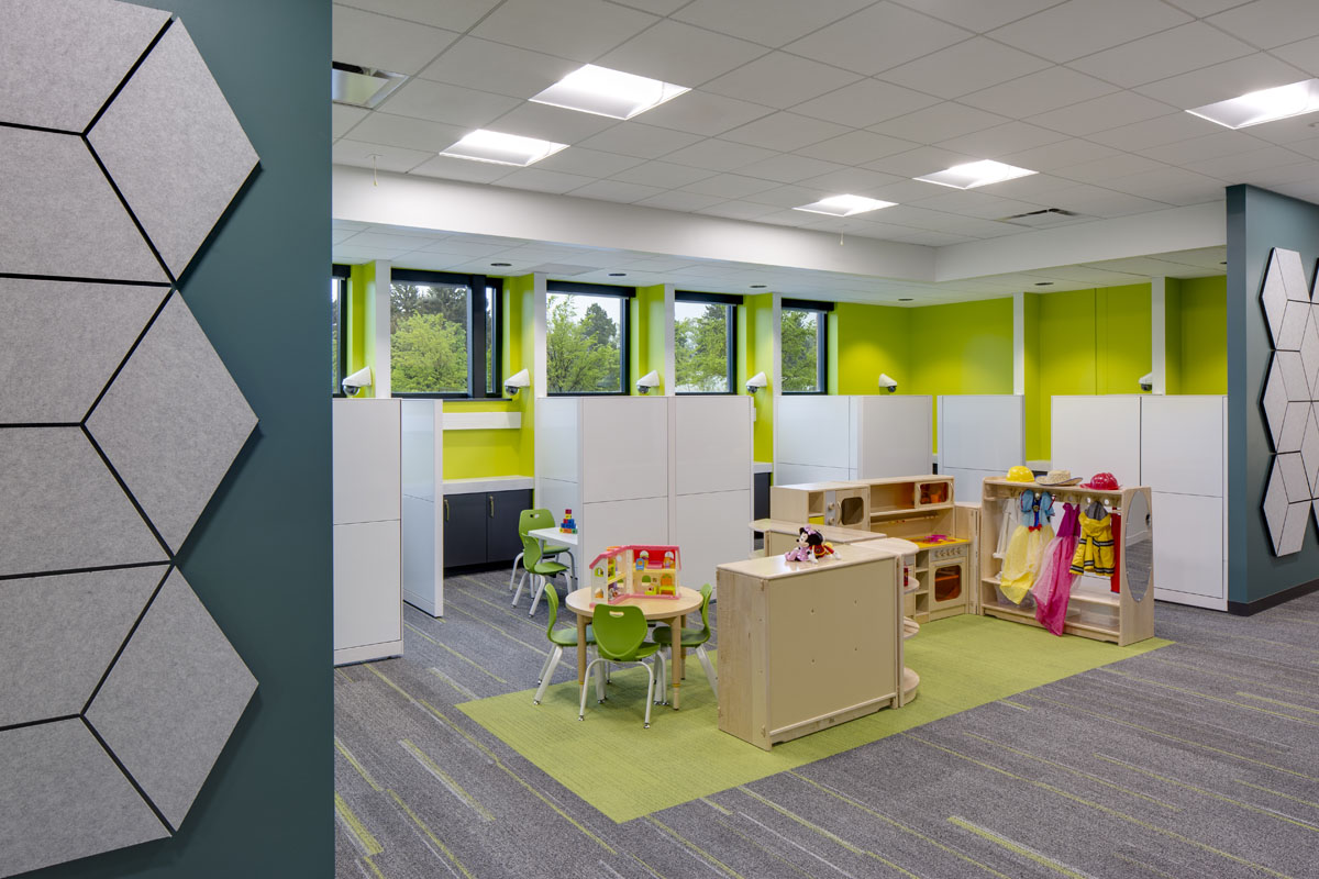 A bright green play area with sectioned stalls is part of the healthcare design.