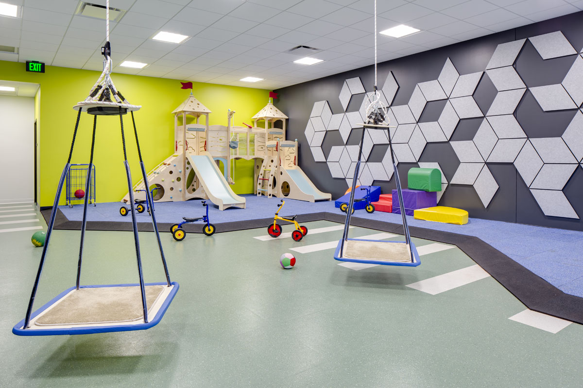 A large room for motor control with tricycles, balance swings, and play structure as part of the healthcare design.