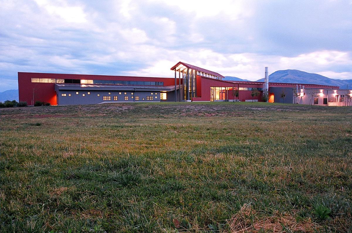 The red and gray barn like Agricultural Teaching and Research Facility from across a field.