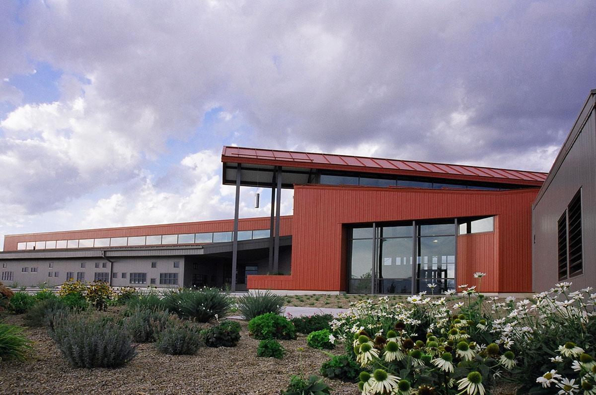 The side of the main entrance to the Agricultural Teaching and Research Facility with red paneling and planted landscape.