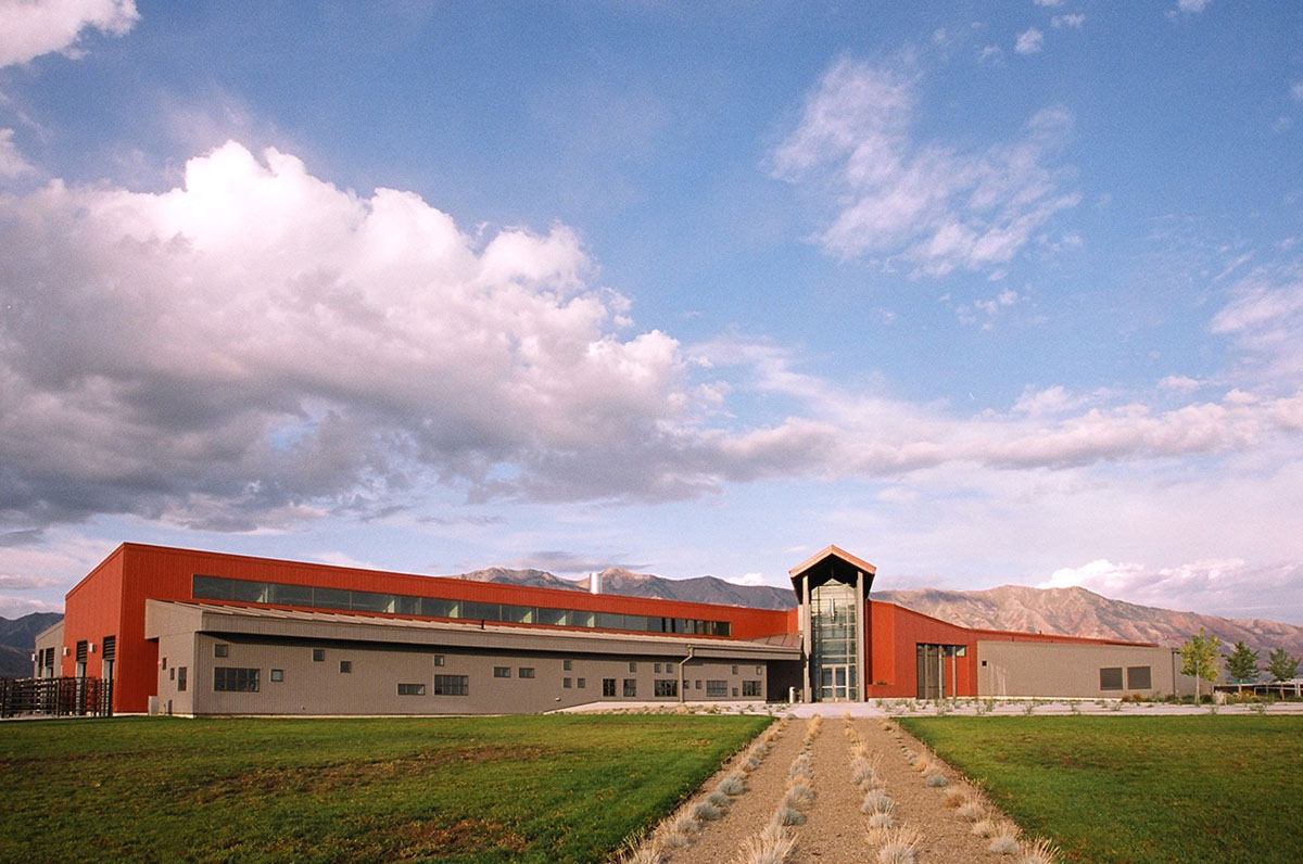 View down a gravel path with grass plants looking towards the main entrance of the Agricultural Teaching and Research Facility.