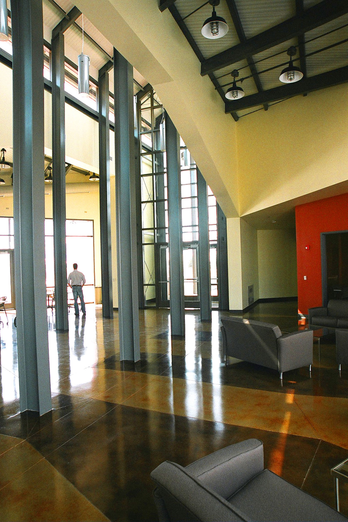 A man stands in the main lobby of the Agricultural Teaching and Research Facility.