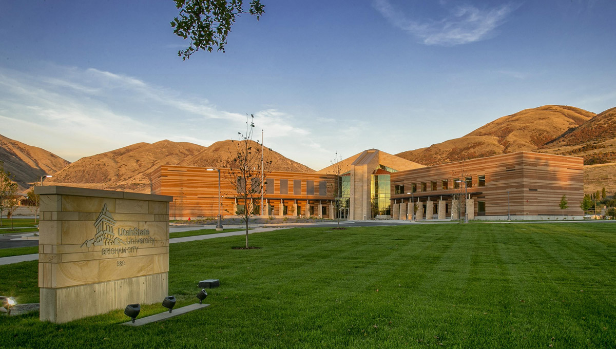 Utah State University Brigham City logo on a sign in the foreground with the classroom and student services building in the background.