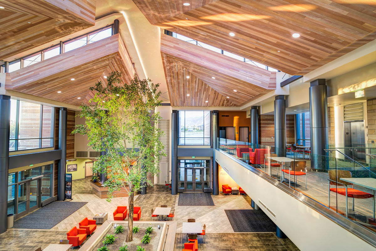 Main lobby of the classroom and student services building with paneled wood ceilings, a tree in the center of the main floor, and seating on an open second story.
