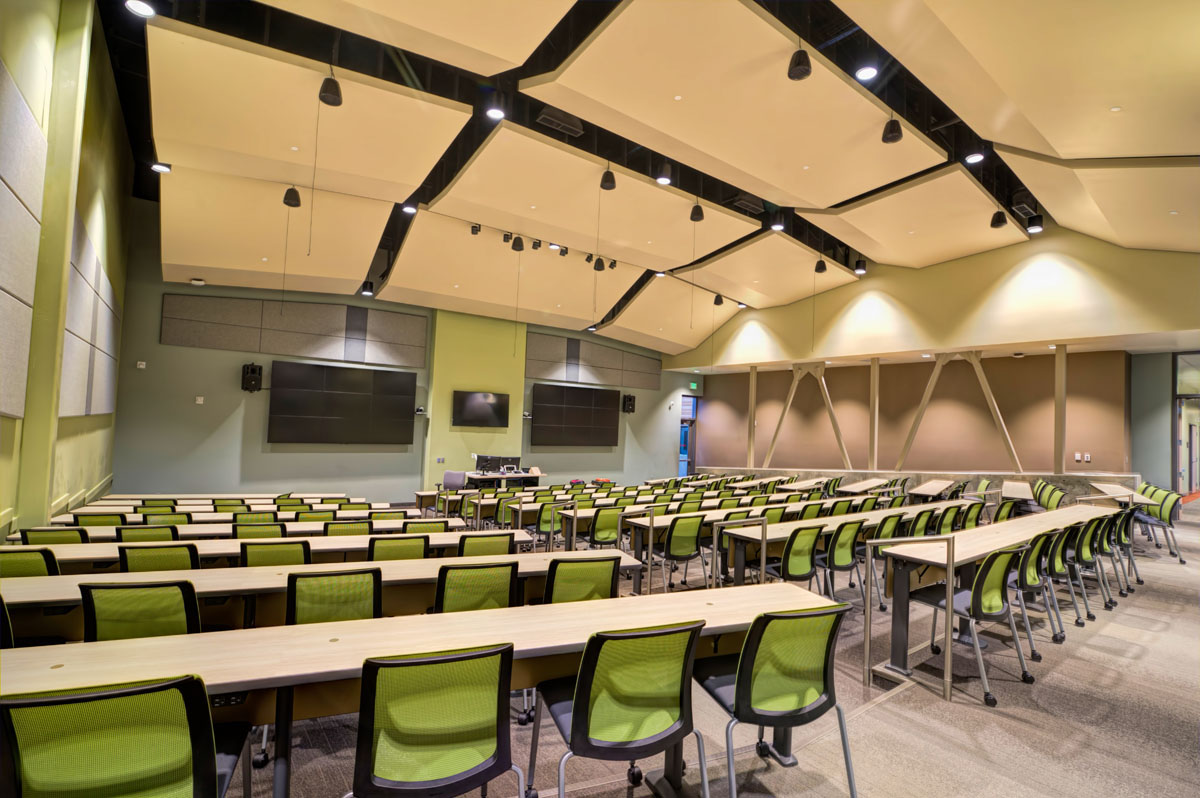 Angled acoustic panels in the ceiling of a classroom lined with desks and chairs in the classroom and student services building.
