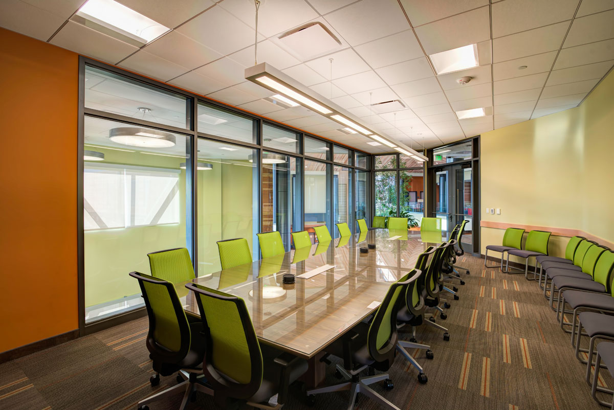 A conference room with a long table and green rolling chairs in the classroom and student services building.