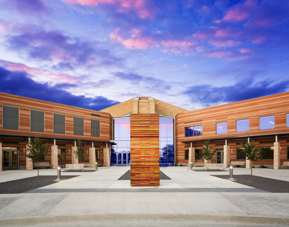 The classroom and student services building at sunset with a colored glass art installment in front.