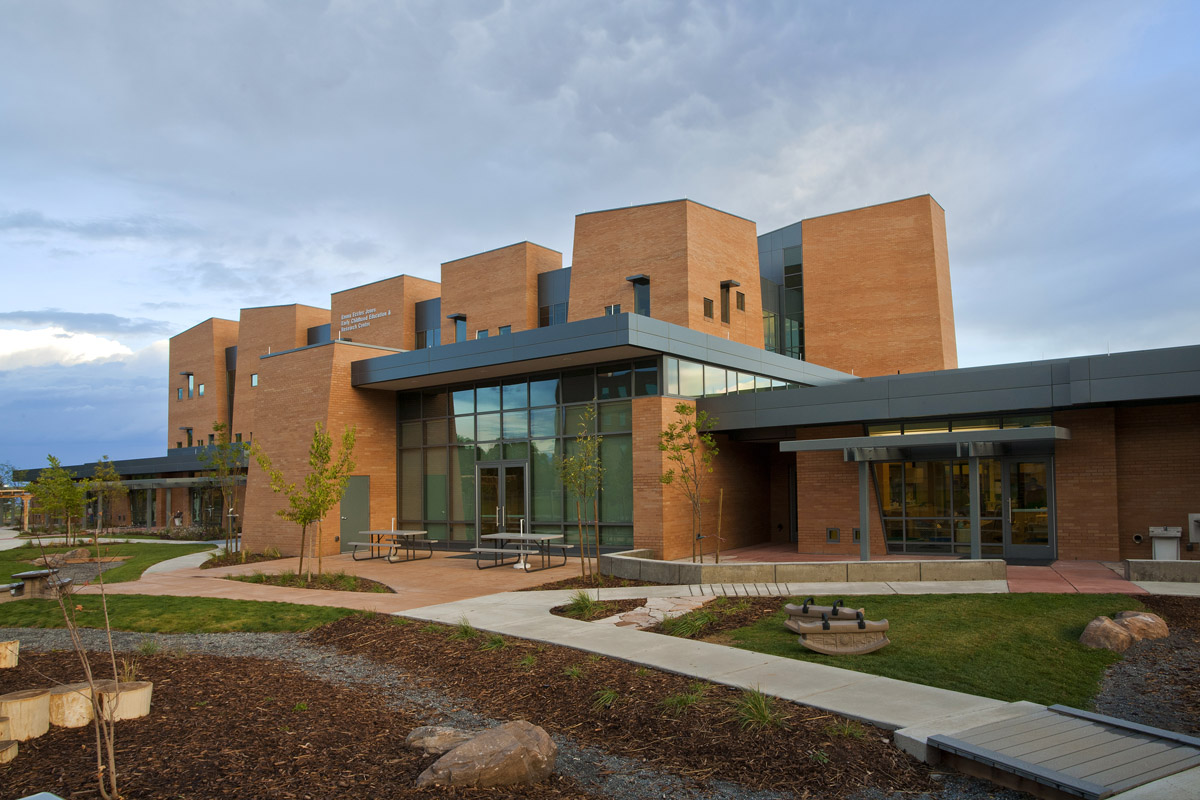 View of the early childhood education center with landscaping including bridged paths and picnic benches.