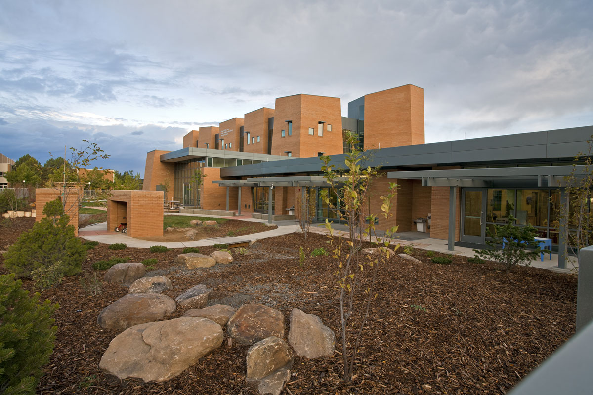 Early childhood education center with mulch and boulder landscaping and a small brick structure for tricycle storage.