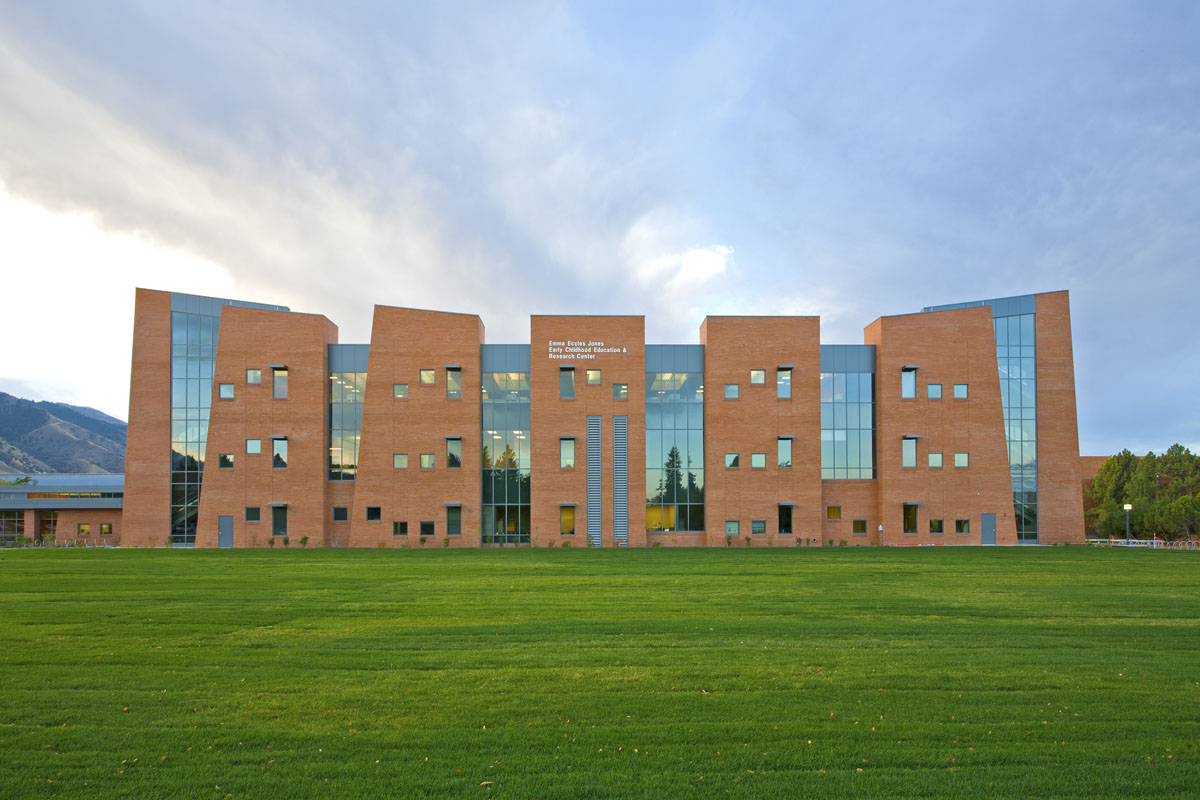 An expansive green lawn in the foreground with the red brick early childhood education building in the background.