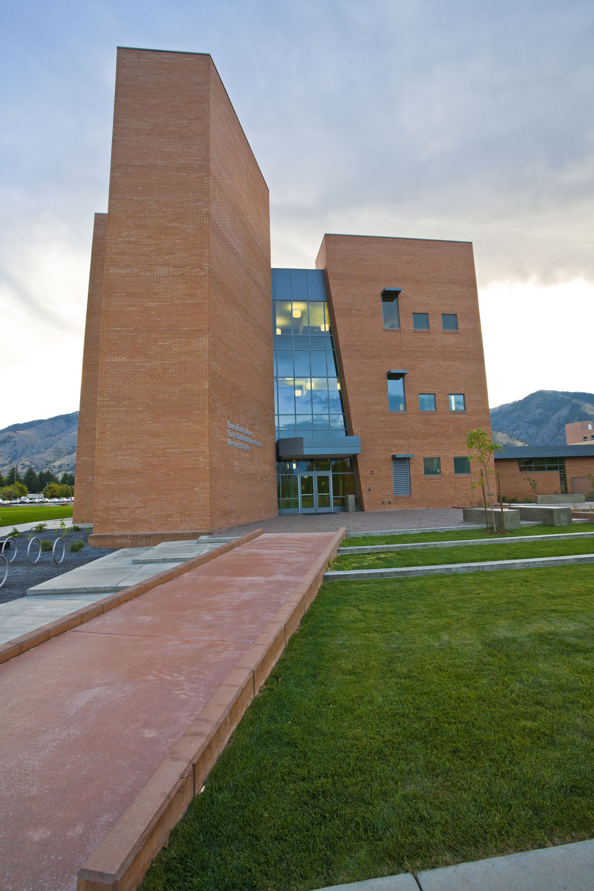 A red stone path cuts across a green lawn leading to the early childhood education building.