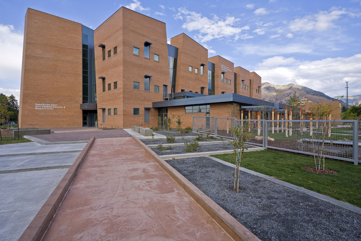 A red stone path cutting at a diagonal towards the building is lined by gravel plant beds with views of the fenced children's play area at the early childhood education building.