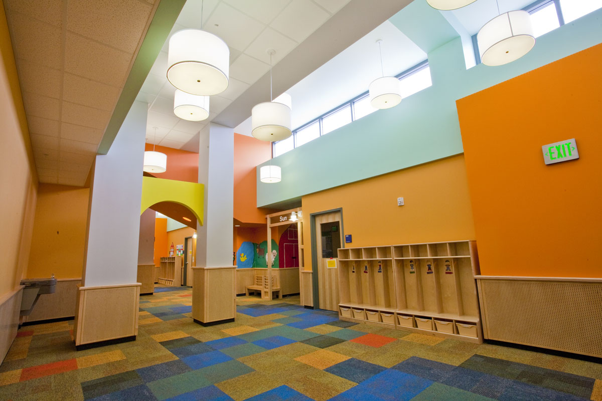 An interior hallway in the early education building shows bright paint on the walls in orange, yellow, and blue hues.