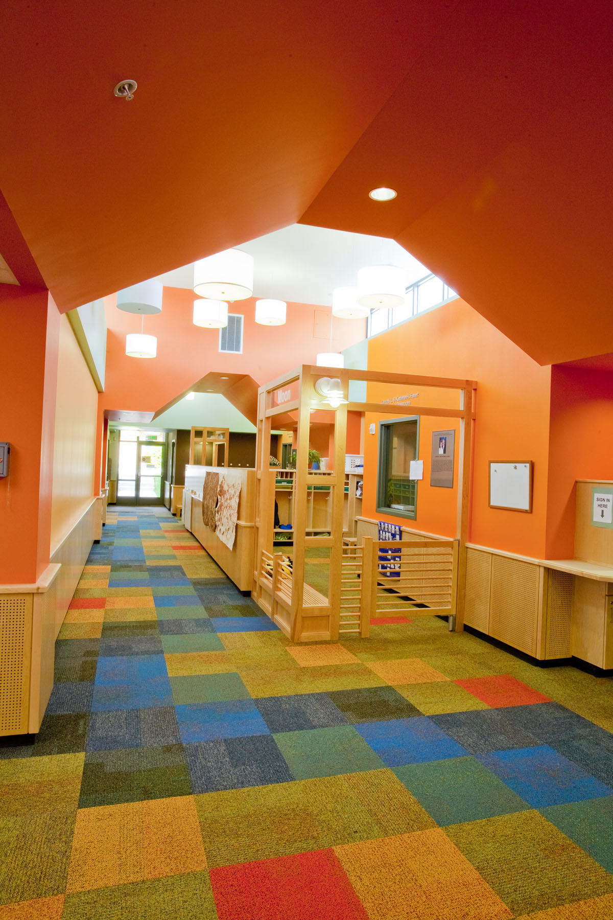 A brightly colored hallway with orange paint on the walls and ceiling in an early childhood education building.