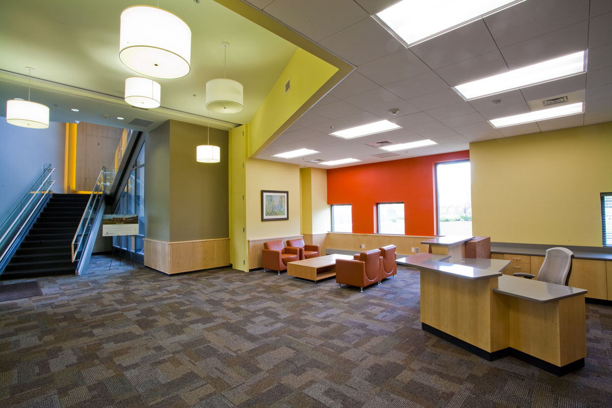 A reception and lobby area show a desk on the right, seating in the middle, and a stairway to the right in the early childhood education building.
