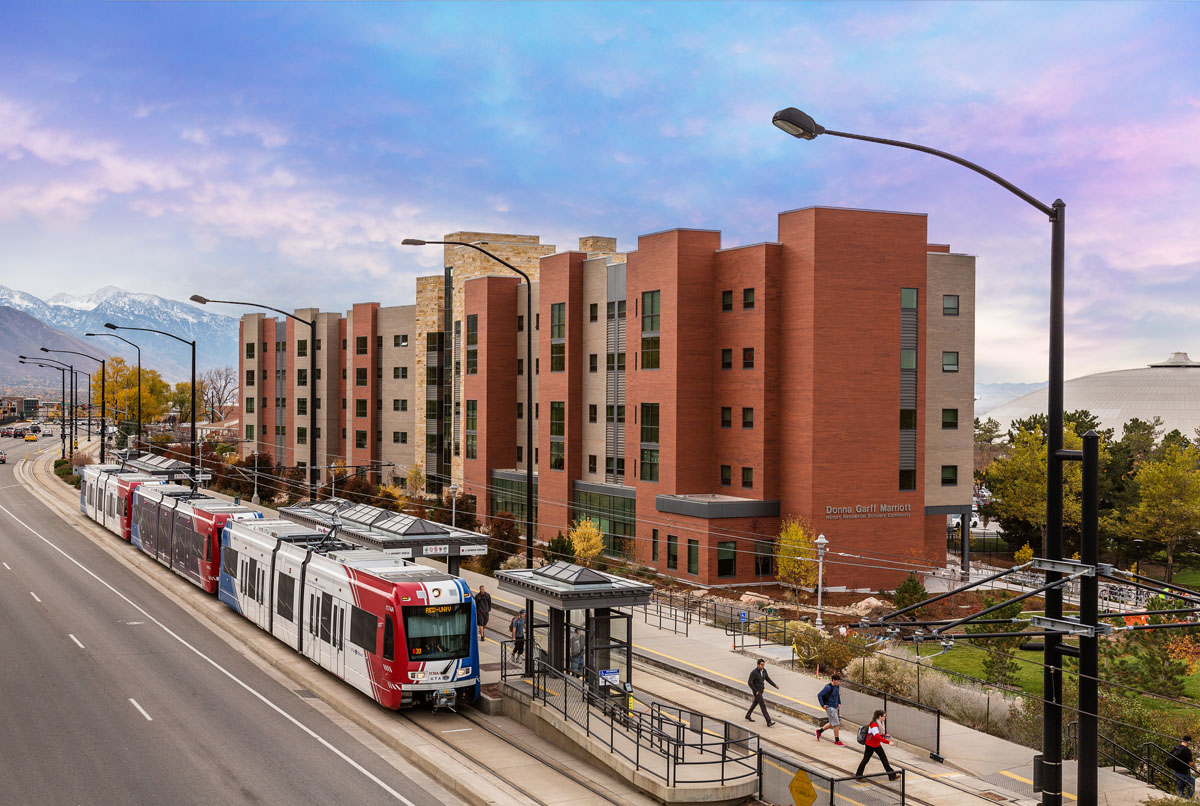 A public transportation trax station shown just behind the honors student housing building.