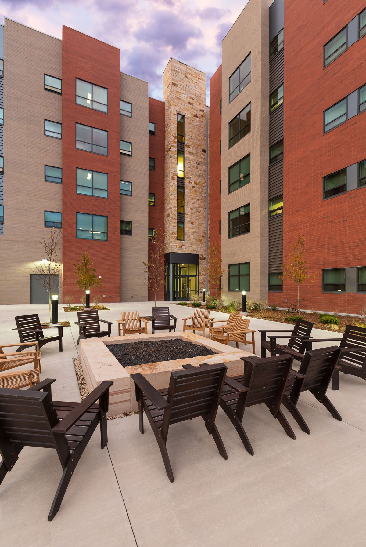 Large, square fire pit with dark and light wood chairs surrounding at the back of the honors student housing building.