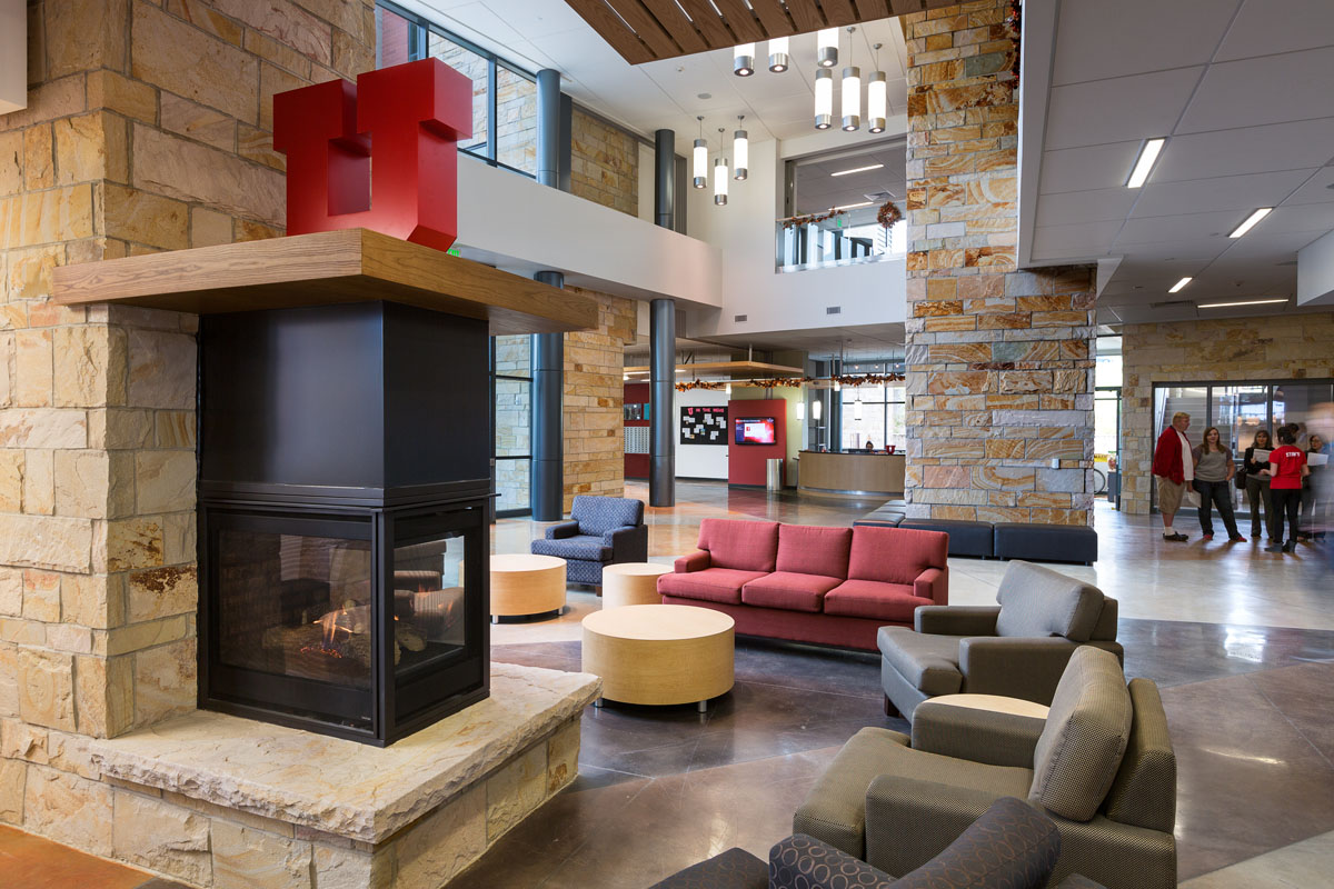 The lobby of the student housing building with fireplace, large U logo, and seating.