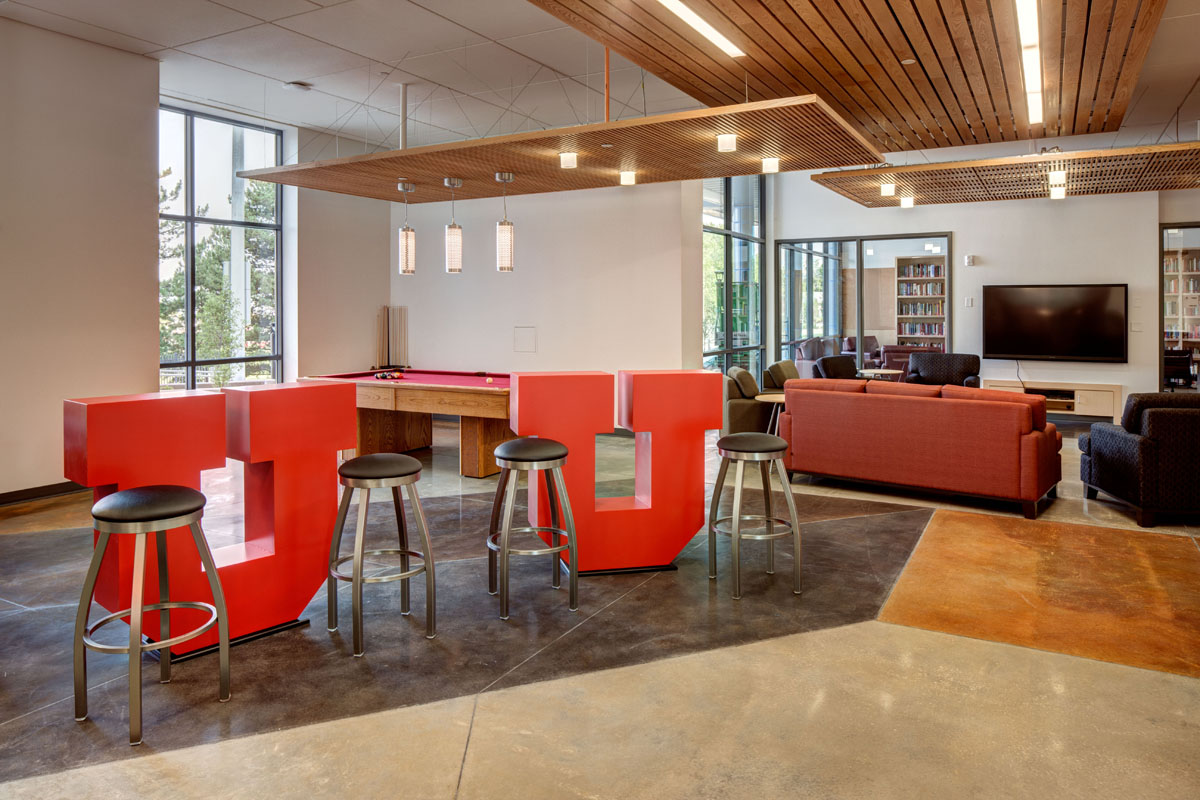 Two large, red U's with bar stools next to them act as tables with a red felt pool table in the back at the honors student housing facility.