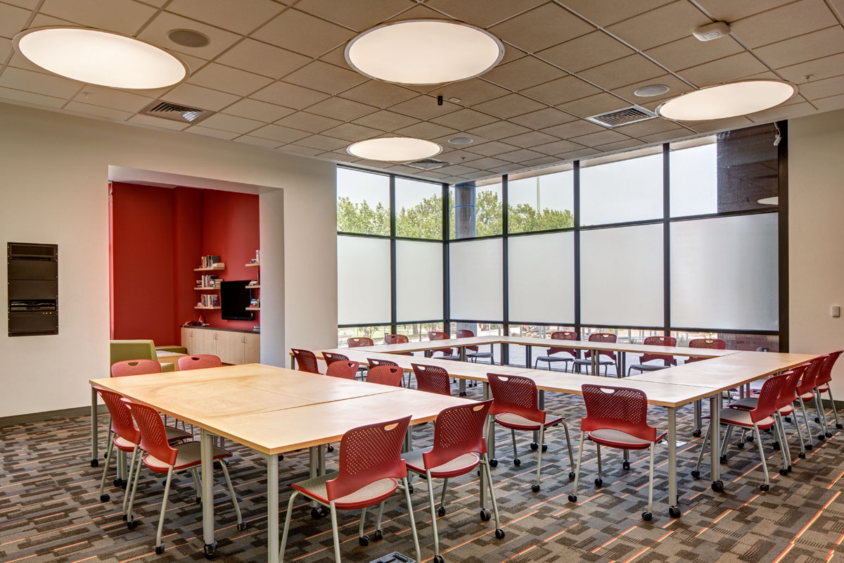 Tables and chairs are arranged over a bold carpet pattern to give students a place to meet and work on projects within the honors student housing building.