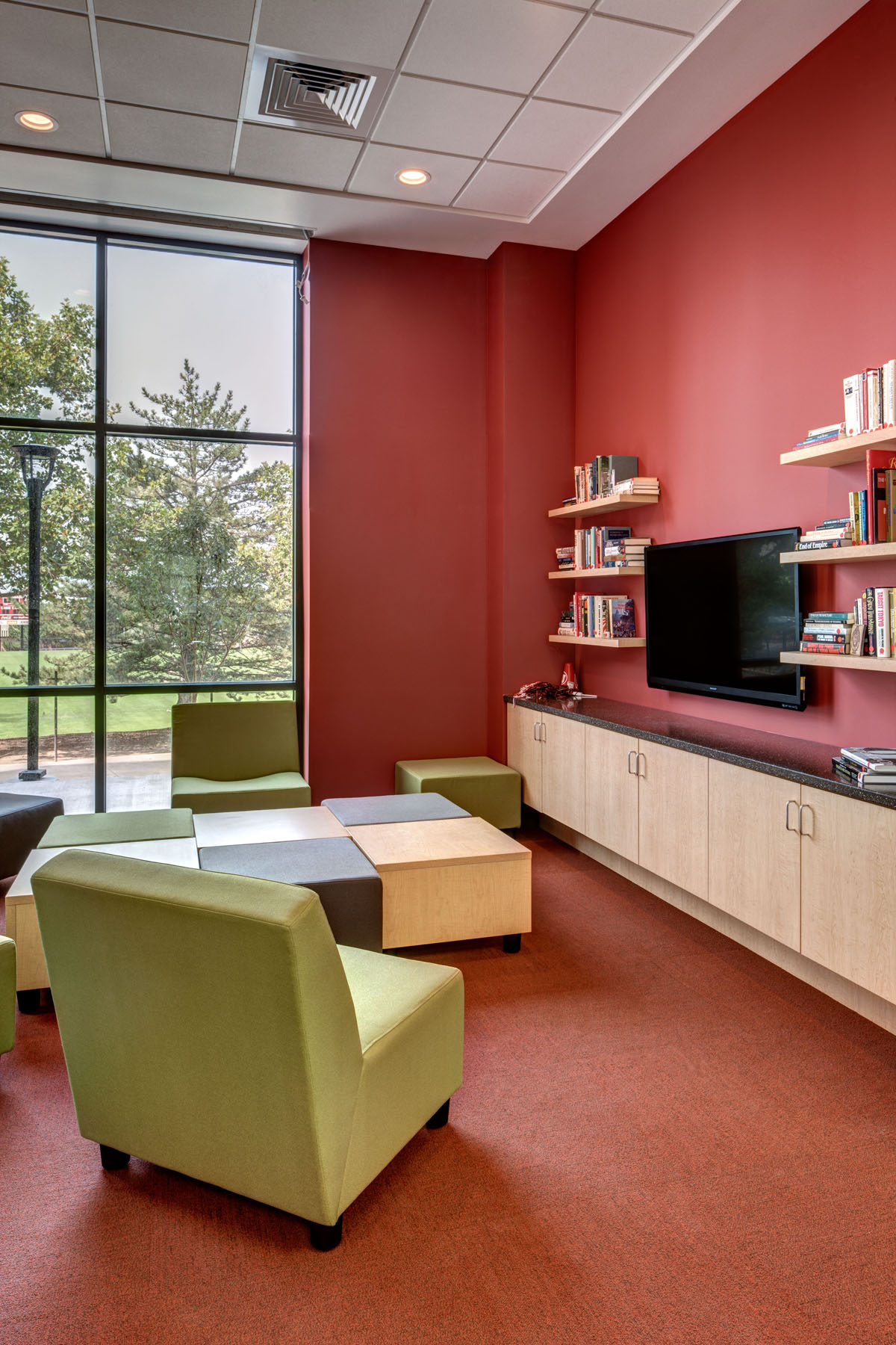 A red entertainment room with green chairs and ottoman squares give students a place to read or watch TV in the honors student housing building.