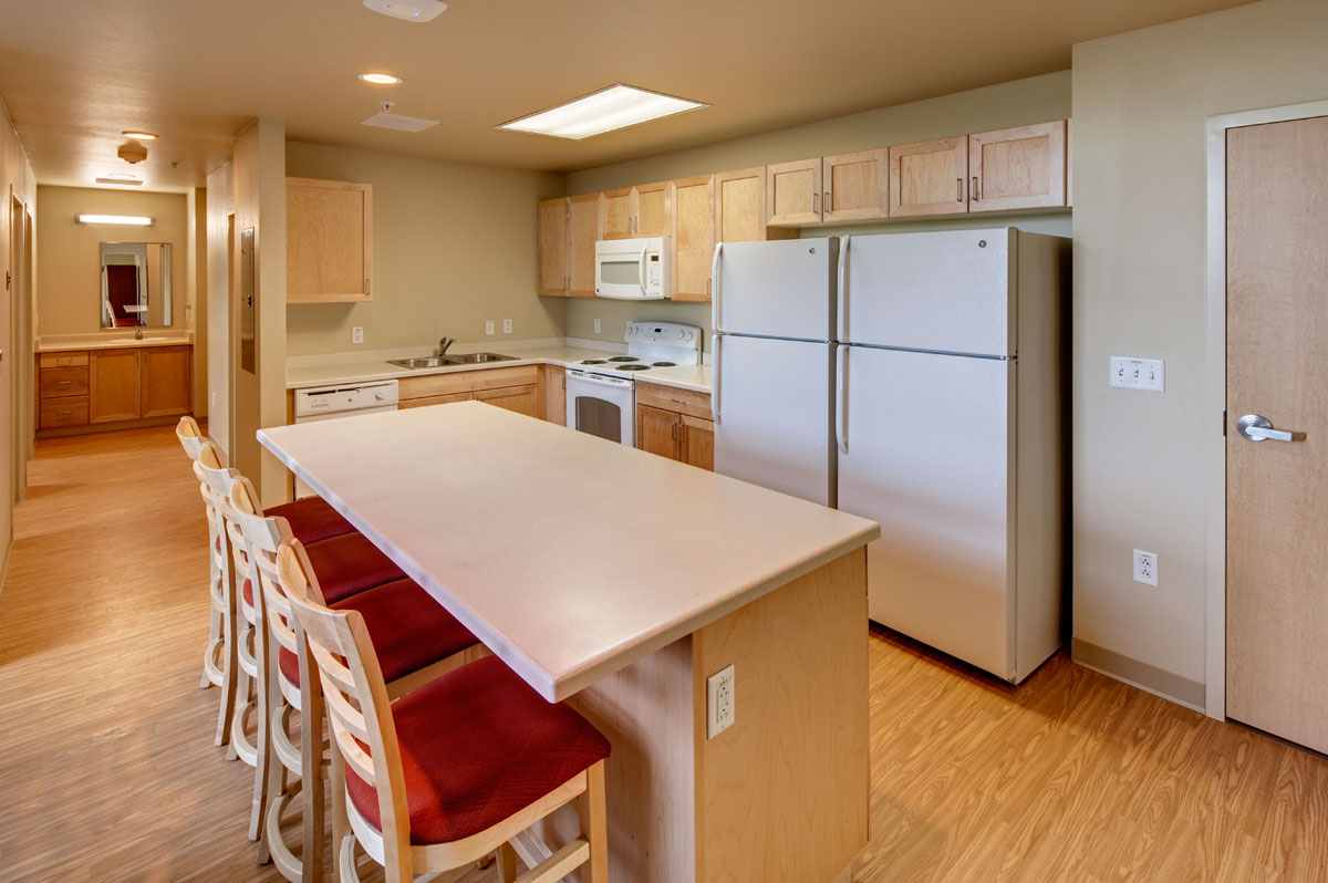 A kitchen in a large dorm room with two refrigerators and four bar stools at the island in the honors student housing building.