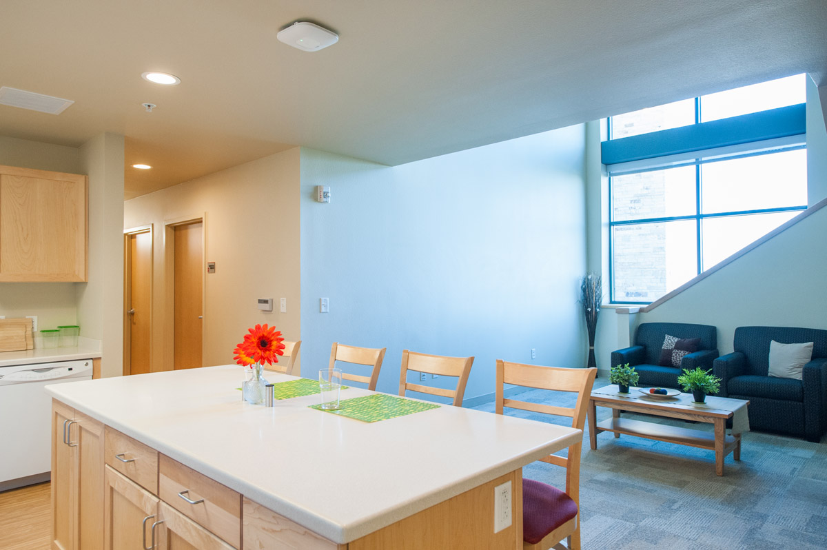 A dorm room kitchen island with four bar stools and a seating area just behind with a window and stairs just beyond that in the honors student housing building.