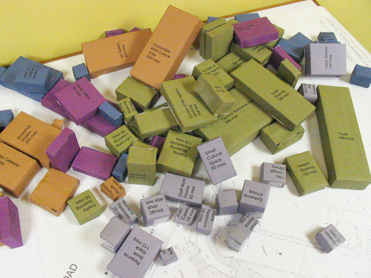 A group of small, colored blocks with room names and square footage on them for the Irish library design competition.