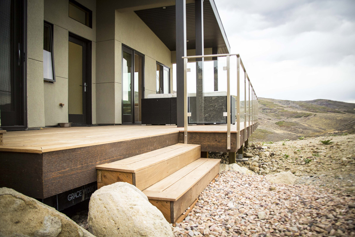 Steps from the deck lead to gravel below with views of the mountains from this modern home.