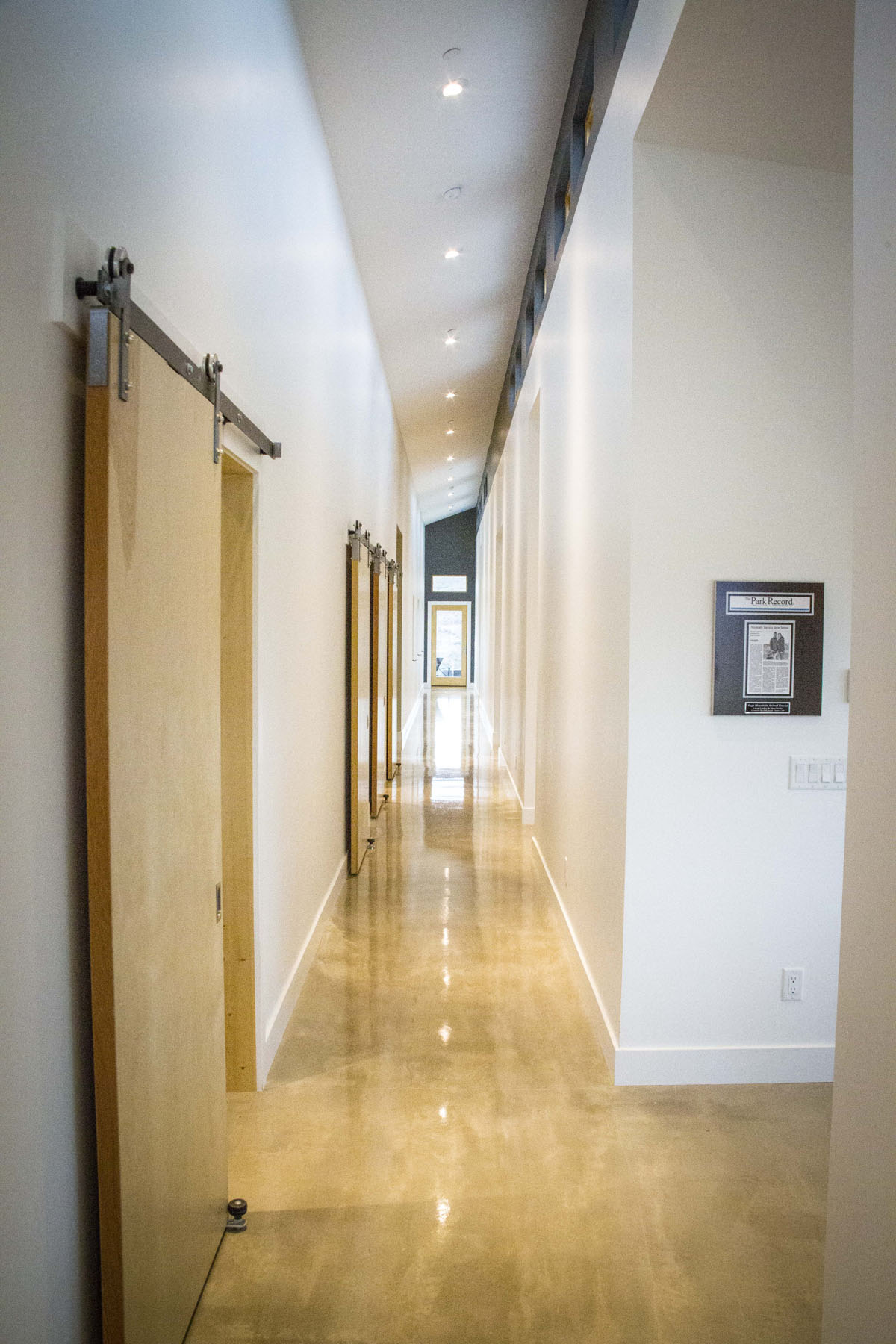 Modern home interior with white walls, polished concrete floors, and sliding barn doors.