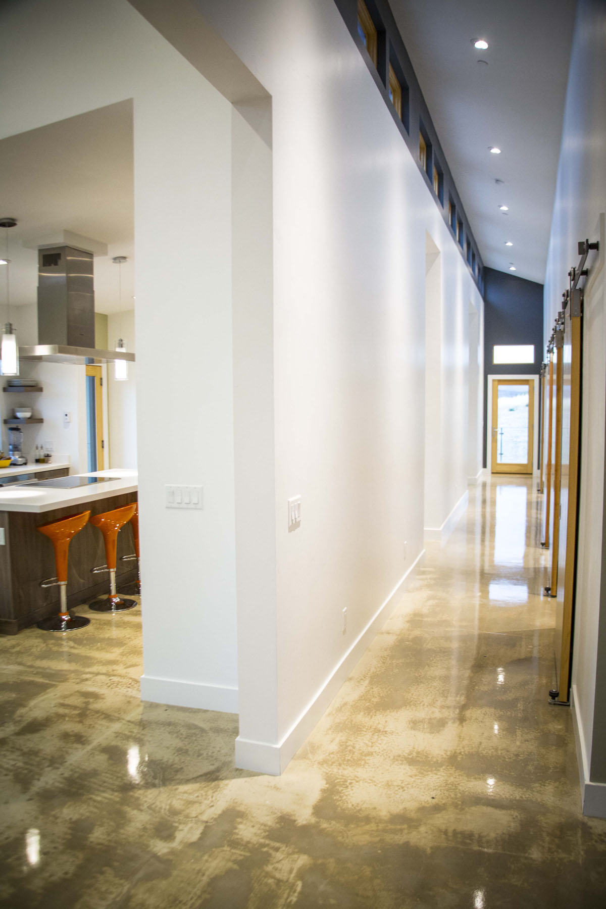 Modern home interior image of hallway on the right and kitchen on the left with orange stools at the kitchen island.