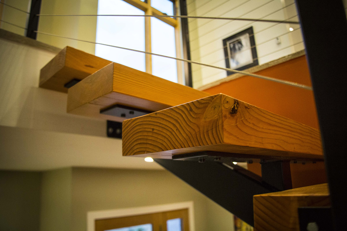 Suspended wood stairs with metal railings in this modern home.