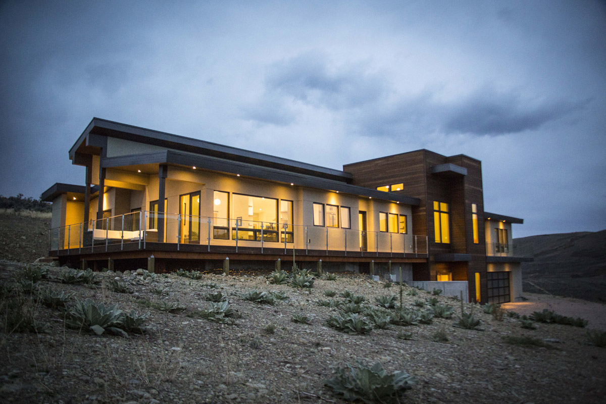 The modern home glows from within at dusk.