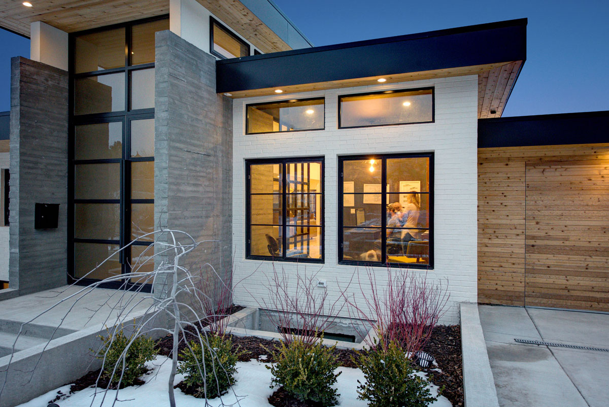 The modern residential design of this house includes black framed windows, wood accents, and white painted brick.