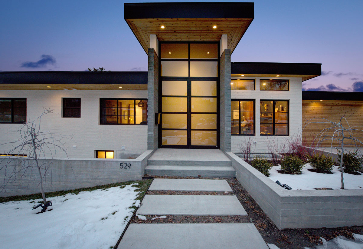 The front of this modern residential design includes a tall, glass front door trimmed in black to match the windows on either side.