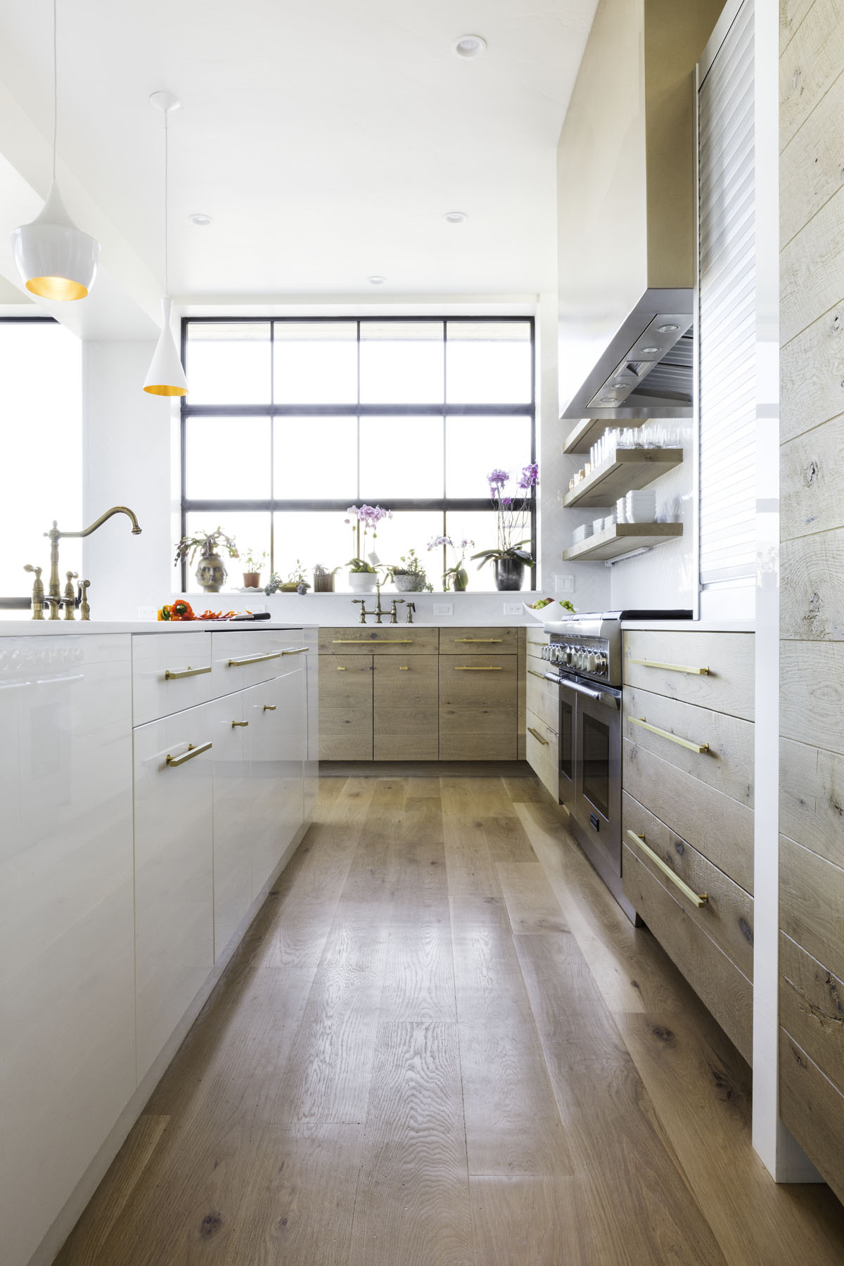A white island with a sink and cabinets to the left faces the stove and more storage to the right in this modern residential design.