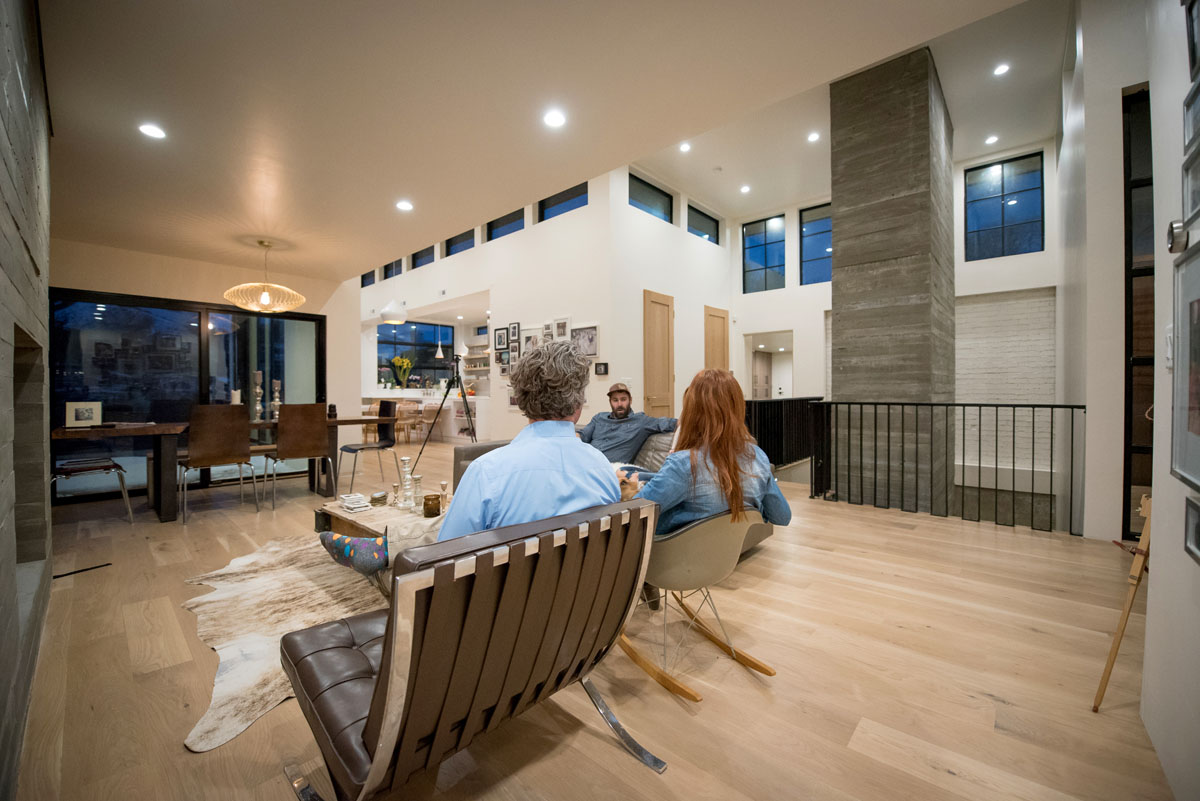 Two men and a woman sit in a living room talking with each other in the early evening inside a modern residential design home.
