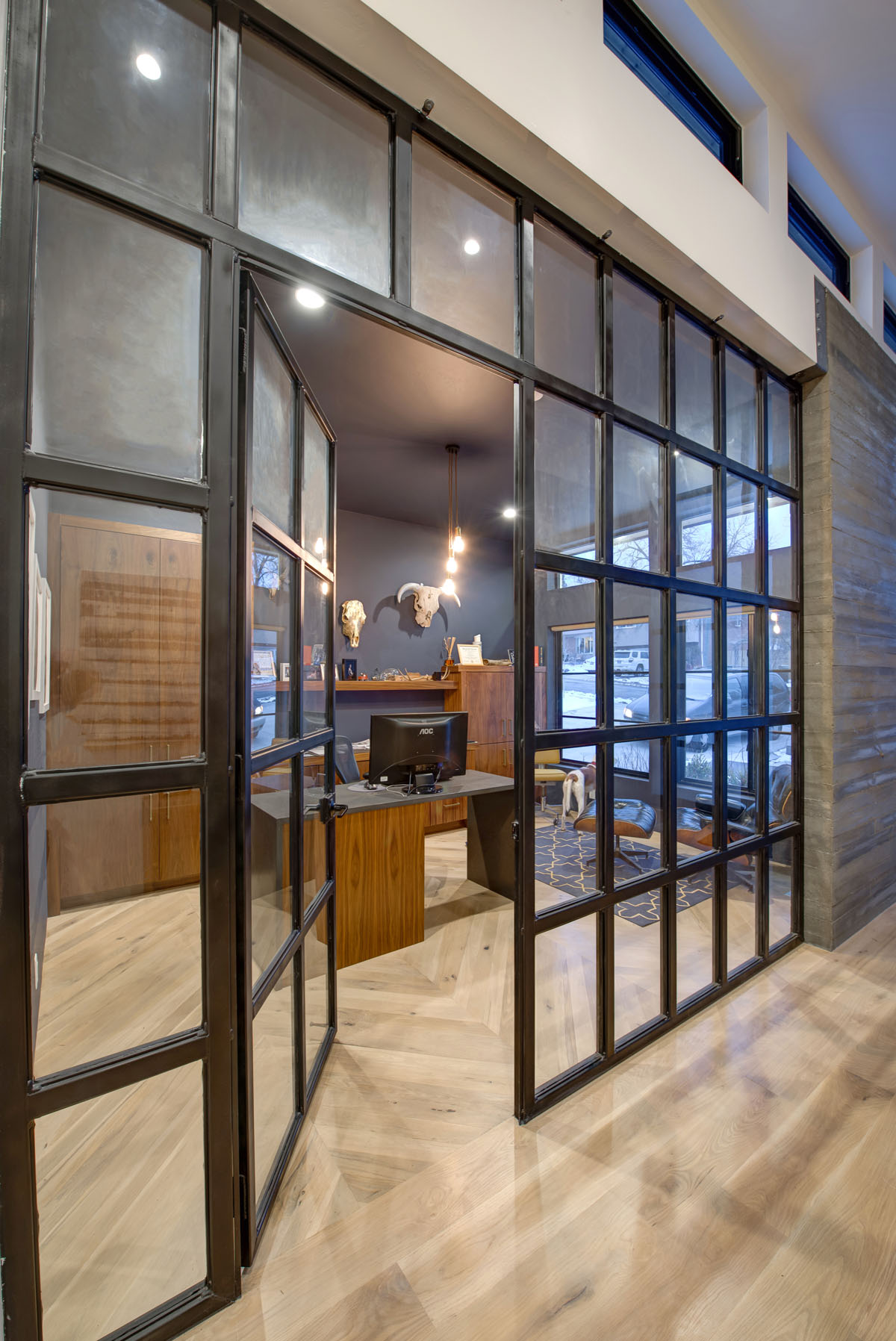 A home office with dark blue walls and ceiling and glass paneled wall and door in a modern residential design home.