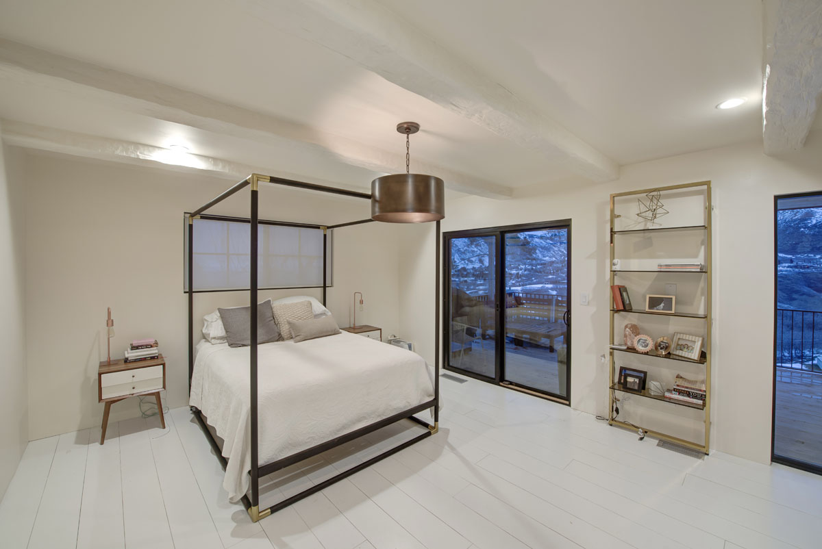 A master bedroom with cream walls and ceiling with white plank floors as part of a modern home design.