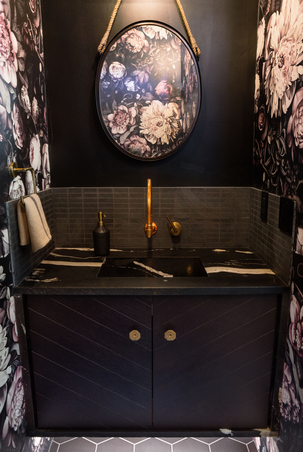 A dark bathroom with flowered wallpaper, hanging oval mirror, black marble topped vanity with gold accents as part of this modern residential design.