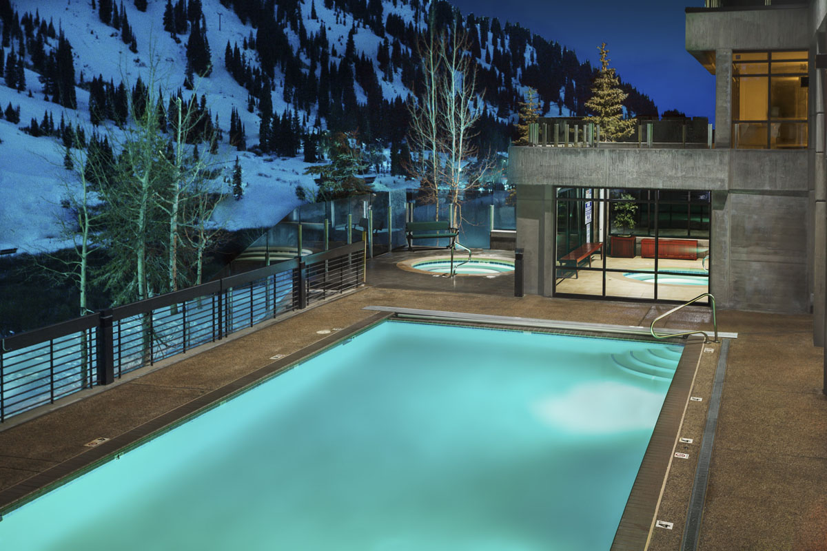 Rustler Lodge deck pool and indoor and outdoor hot tubs at dusk.