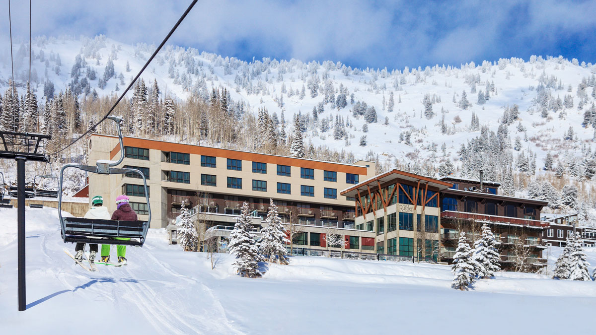 Two skiers in a ski chair ride past the Rustler Lodge.