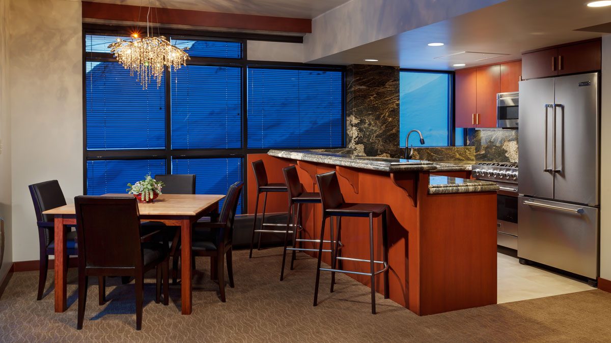 Hotel room at the Rustler Lodge with a kitchen, bar stools, and dining table with a large window with views of the mountain in the background.