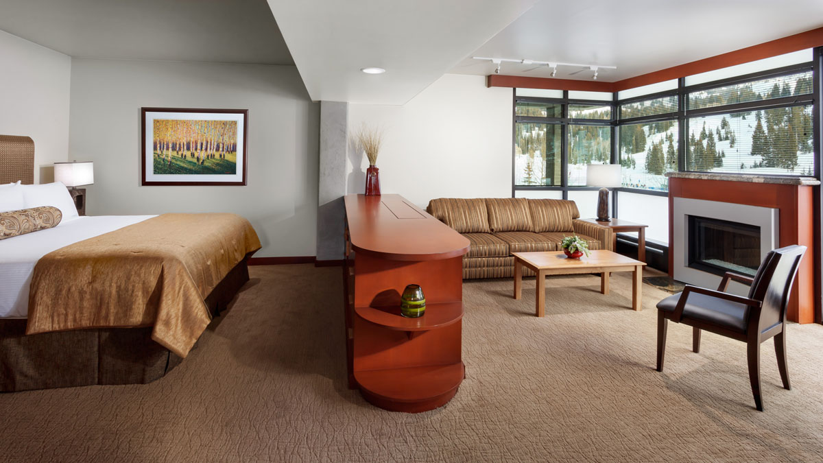 Large hotel room at Rustler Lodge with bed on the left, a wood cabinet with a TV that rises from within, and a couch and fireplace to the right.