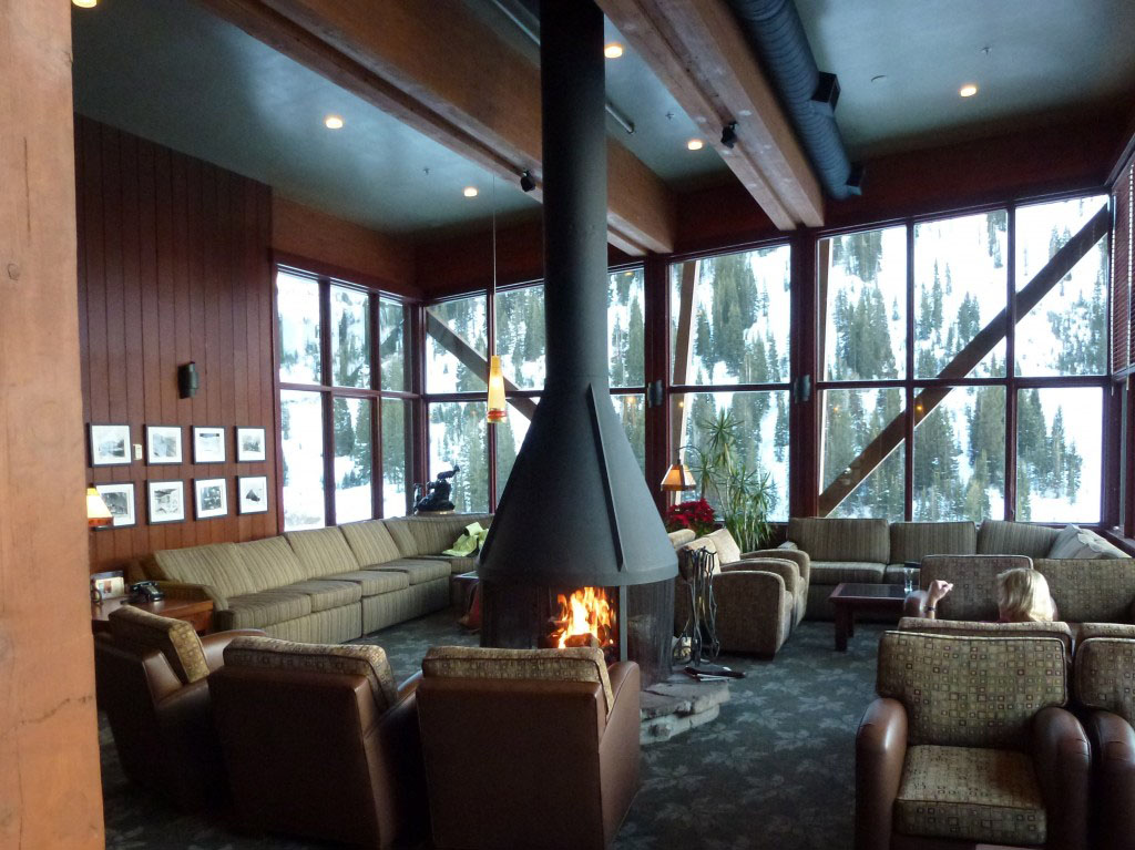 Wood paneled lounge room at Rustler Lodge with a fireplace in the center and couches and chairs surrounding.