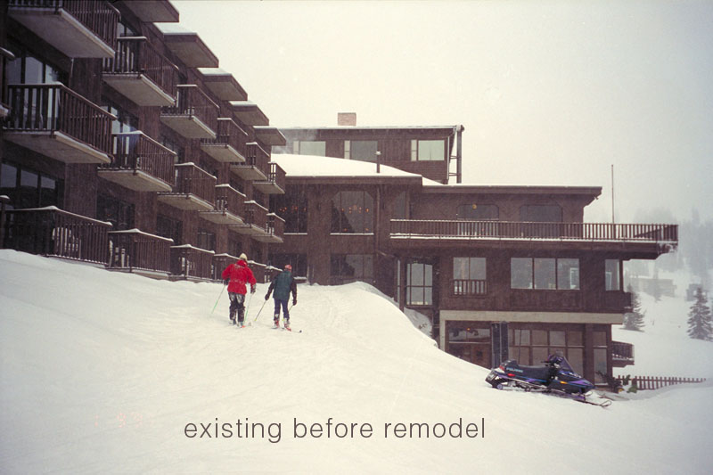 Two skiers ski up towards the Rustler Lodge as it looked before the remodel with predominantly dark brown colors.